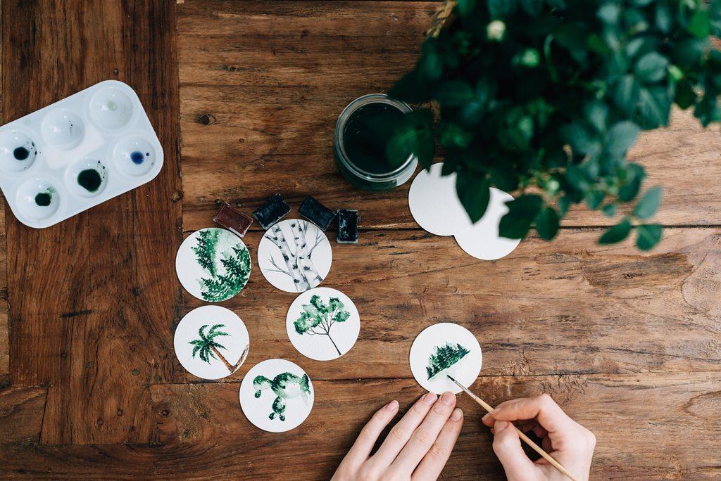 Main en train de peindre des motifs végétaux sur des étiquette rondes et une table en bois